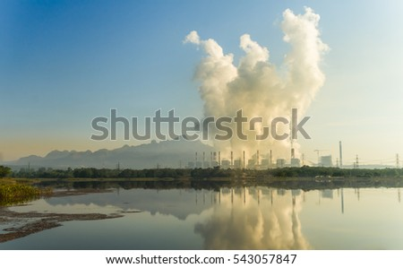 Hot steam from chimney at coal power plants against blue sky.