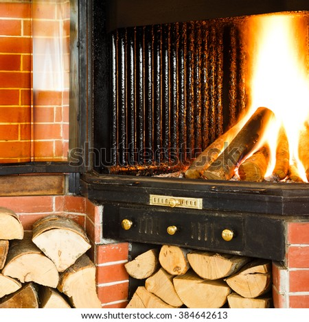 Hot wood fire burning in a chimney insert for heating a home or house in winter using natural renewable resources for fuel with stacked wood below on a brick wall.