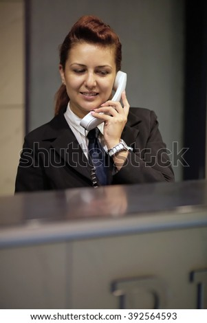 Hotel Concierge. Reception of hotel, desk clerk, woman taking a call and smiling.