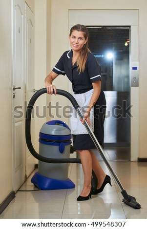 Hotel maid with vacuum cleaner during housekeeping