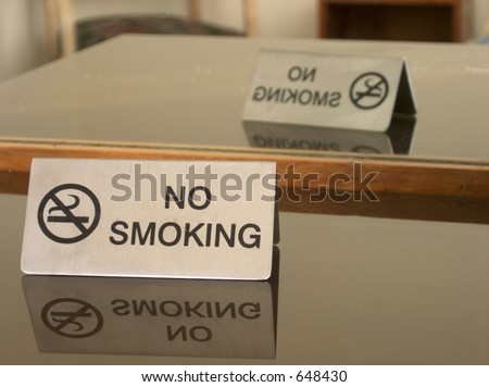 Hotel room no smoking sign reflected on glass surface and in mirror.