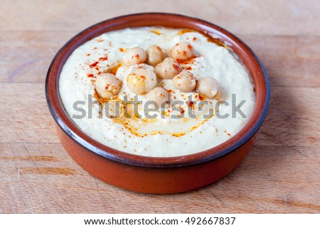 Houmous dip topped with paprika and chickpeas in a terracotta dish