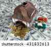 House and cars models are placed on a surface covered with dollar bills symbolize Invest in real estate and win concept - stock photo