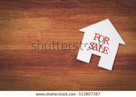 house for sale symbol with wood background
