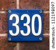 house number three hundred and thirty. White lettering on a blue background. - stock photo