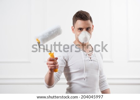 House painter, young handsome man wearing safety mask showing roller and smiling, selective focus shot over the white wall background
