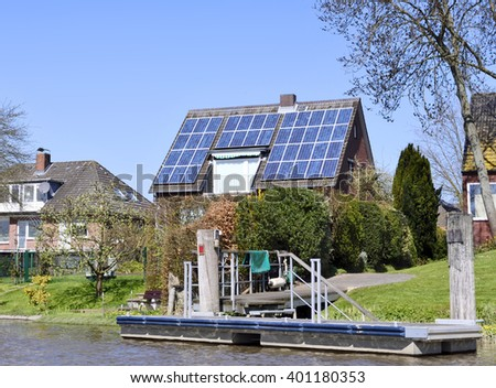 Houses on a river with jetty or little pier. Solar panels, solar energy on the roof of a house.