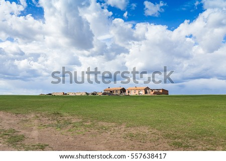 houses on green grassland under blue sky with beautiful cloudscape