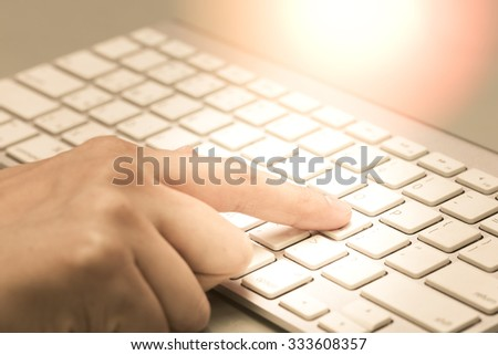 Housewife doing online banking, online shopping, making a payment or purchasing goods on the internet entering her credit card details on a pc, close up view of her hands.