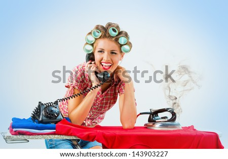 Housewife talking on the phone while ironing blue background