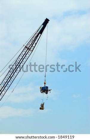 How's It Hangin'? - A crane lifts expensive construction equipment overhead to ward off theft.