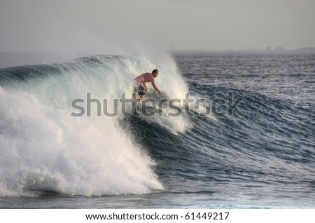 HUDHURANFUSHI ISLAND,MALDIVES-JUNE 29:Unidentified man surfing on huge wave of Indian Ocean of Maldives on June 29, 2009 in Hudhuranfushi. The island is a popular place for surfers from over the world