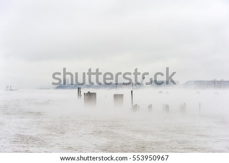 Hudson river in Winter with Misty Edgewater Cityscape in Background.