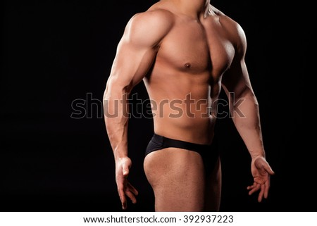 Huge athlete's side pose. Bodybuilder in briefs posing. Demonstrate the best quality. Learning how to pose.