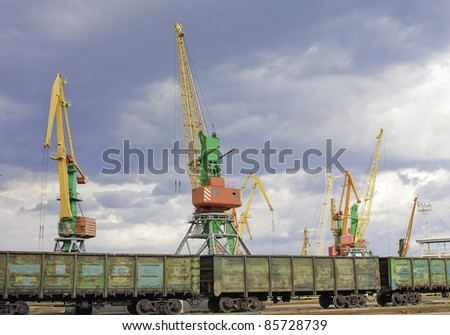 huge seaport cranes in front of railway with wagons