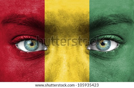 Human face painted with flag of Guinea