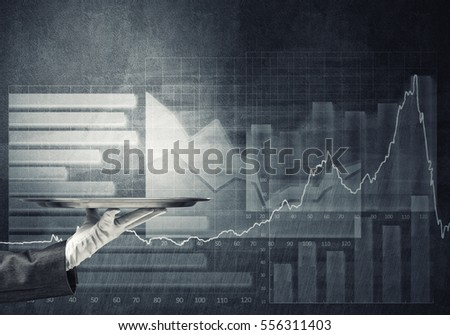 Human hand holding silver plate and graphs at background