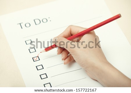 Human hand writing on a checklist document