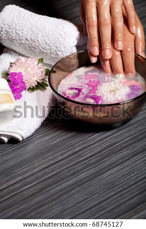 Human hands in bowl with cosmetic oil and chrysanthemum flowers. Beauty treatment in spa salon