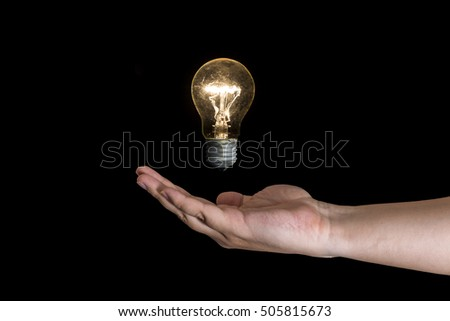 Human nad holding a lightbulb isolated on a black background. Having an idea concept.