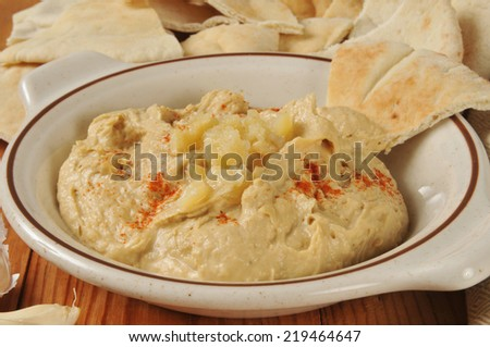 Hummus with garlic and red pepper and pita bread wedges