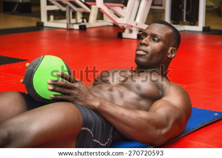 Hunky muscular black bodybuilder working out in gym, exercising abs laying on the floor