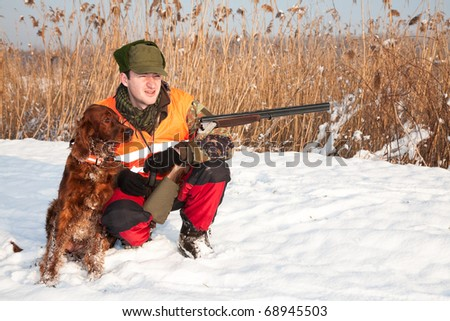 Hunter and his dog before the hunt. General winter open season photograph. The hunter wears a highly reflective vest to be seen from the other hunters