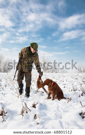 Hunter getting the pheasant from the dog during a winter hunting party. General open season scene