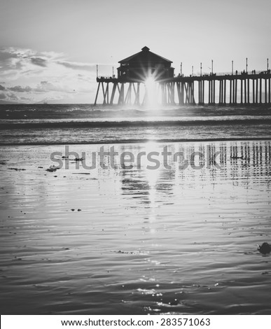 Huntington Beach Pier in Orange County California at Sunset with reflection processed in vintage black and white