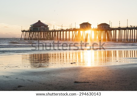 Huntington Beach Pier Sunset at Low Tide with Reflections in Water and Sunburst