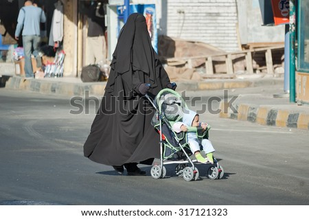 Hurghada, Egypt - November 7. 2006: Arabic mother in burqa conducts carriage with child