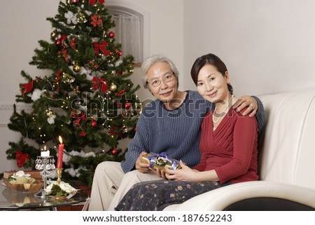 husband and wife sitting on sofa in front of tree