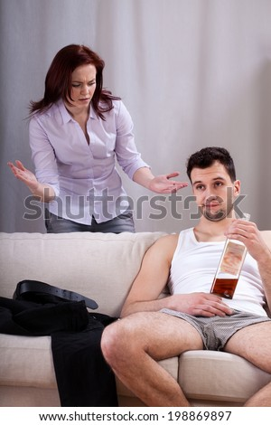 Husband drinking whiskey and ignoring his talking wife