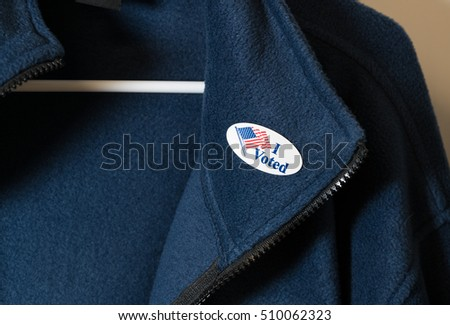 I Voted sticker with USA flag on blue jacket on hanger after getting home from the vote for President