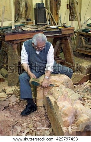 IBARRA, ECUADOR - CIRCA MARCH 2016: Man carving a religious statue with a hammer and chisel in a workshop in San Antonio de Ibarra