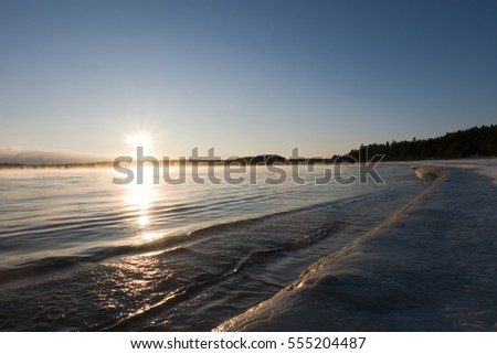 "Ice and non-freezing abnormally warm ""boiling"" water in extremely cold on winter sunset backgrounds, January, Lake Ladoga, Karelia, Russia. It is the largest freshwater lake by area in Europe."