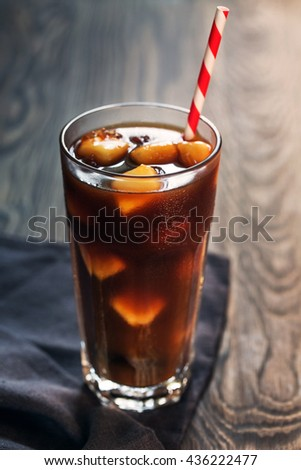 Ice cold coffee with milk ice cubes and straw on wooden background, close up