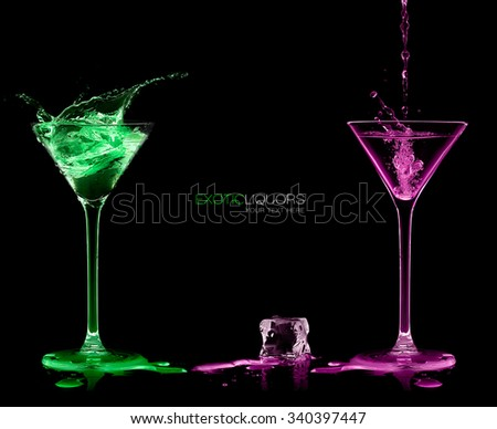 Ice cube between two cocktail glasses filled with green and pink alcoholic exotic liqueur splashing out, with copy space on black, concept of style and celebration. Template design with sample text