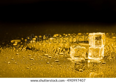 ice cubes and water drop on light golden background.