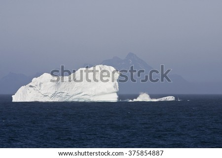 Iceberg Floating in Ocean with Mountains in the Background