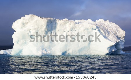 Icebergs of Greenland at a short distance. Huge masses of thawing ice. Deep-water fjords of Greenland.