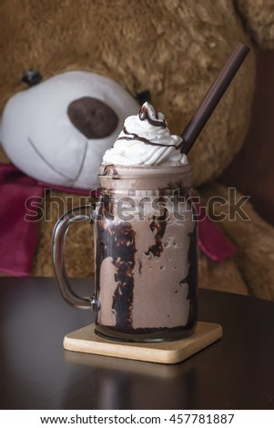 Iced chocolate smoothie with whipped cream in glass bottle on wooden table