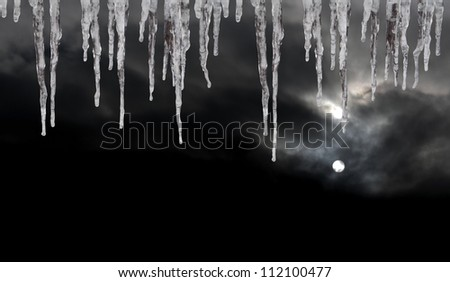 Icicles with dark sky and cold moon in background