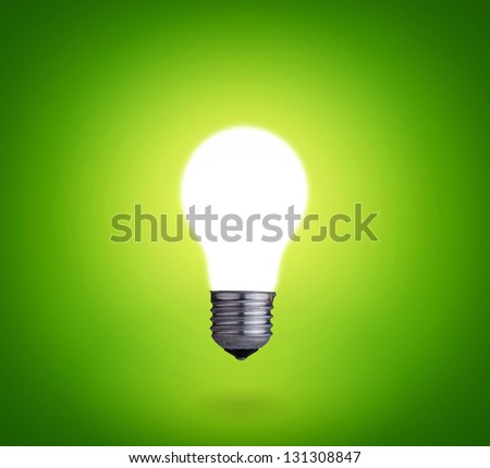 idea concept whit one glowing light bulb on green background