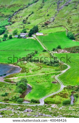Idyllic landscape in the countryside of Ireland with a farm road between the green hills.