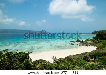 Idyllic tropical beach paradise blue lagoon full of clear water and healthy coral on stunning white sand beach with greenery.