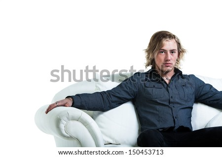 image of a caucasian man with long blond hair dressed in a navy dress shirt relaxing on a white sofa looking impassive