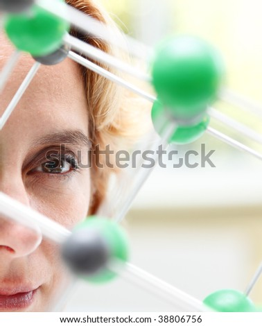 Image of a female researcher eye through a molecular model structure.Selective focus on the eye.