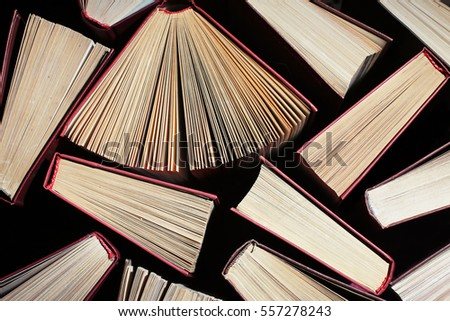 image of a stack of hard back books on the end of the pages toned with a retro vintage warm filter, 