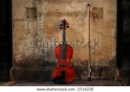 Image of a violin against an old concrete wall.